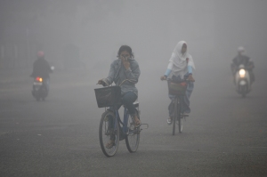 Residents cycle through the haze-blanketed town of Sampit, in Indonesia's Central Kalimantan province September 28, 2012. The haze that blanketed Sampit is believed to have originated from forest fires and land clearing for plantation use by residents, local media reported. REUTERS/Sigit Pamungkas (INDONESIA - Tags: ENVIRONMENT SOCIETY) - RTR38J1I